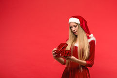 Girl on a red background holds gift box Royalty Free Stock Image
