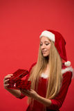Girl on a red background holds gift box Stock Photos