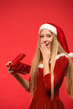 Girl on a red background holds gift box Stock Images
