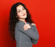 Girl on red background, long curly hair, beautiful portrait Royalty Free Stock Images