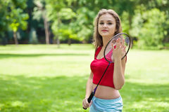 Girl in red with badminton rocket. In park Royalty Free Stock Photo