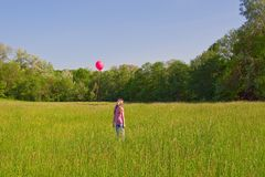 Girl with a red balloon Stock Photography