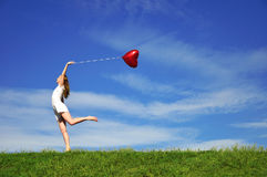 Girl with a red balloon in the form of heart Royalty Free Stock Images