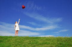 Girl with a red balloon in the form of heart Royalty Free Stock Photo