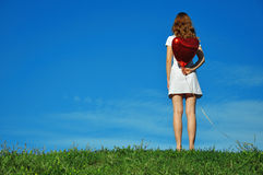 Girl with a red balloon in the form of heart Stock Photography