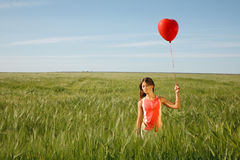 Girl with the red balloon  stands on  the field Stock Photos