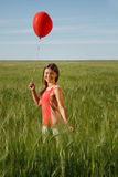 Girl with the red balloon  stands on  the field Royalty Free Stock Image