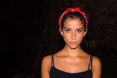 Girl with red bandanna. Photo of a girl with a red bandanna and a sleeveless black shirt staring serious at the camera Stock Image