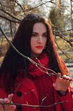 Girl in red among the bare branches of trees Royalty Free Stock Image