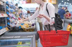 Girl with red basket standing at the checkout in the supermarket. Focus on shopping cart royalty free stock images