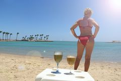 Girl in red bathing suit sunbathing standing on beach by sea. Beautiful woman. In red modern swimsuit enjoying rest by sea. Two glasses of chilled beer on table stock photography