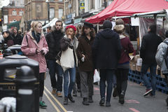 Girl in red beret and man with long hair in black hat dressed in cool Londoner style walking in Brick lane, a street popular among Stock Photos