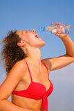 Girl in red bikini drinking water Stock Photos