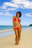 Girl in a red bikini on a Hawaii beach. A beautiful young Polynesian girl in a red bikini on a Hawaii beach at midday with a flower in her hair Royalty Free Stock Image