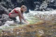Girl in red bikini sits on rock and touches seawater. Girl in red bikini on rocky seashore. Young female person in swimsuit sits on rock and touches seawater royalty free stock images