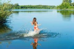 Girl in red bikini run into water Stock Photos