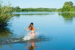 Girl in red bikini run into water Royalty Free Stock Photography