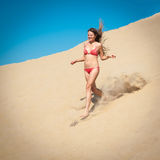 Girl in red bikini running on sand Royalty Free Stock Images