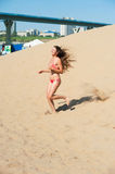Girl in red bikini running on sand Royalty Free Stock Photos