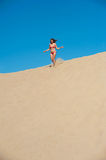 Girl in red bikini running on sand Royalty Free Stock Photography