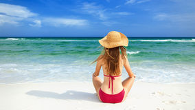 Girl in red bikini sitting on white sand beach Royalty Free Stock Photos