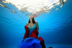 The girl with a red and blue cloth in her hands floats underwater to the surface of the sea from the bottom. Portrait. Shooting under water. The landscape view Stock Photo