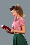 Girl with red book on gray background Stock Images