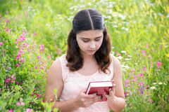 Girl with red book on nature. Romantic girl reading a book on a nature Royalty Free Stock Photography