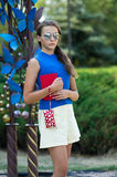 The girl with the red book and a red handbag. Stock Photos