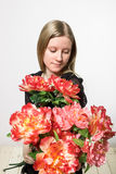 A girl with red bouquet. A blonde girl enjoys red flowers Royalty Free Stock Photo