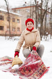 Girl in red cap cleans carpet with snow Stock Image