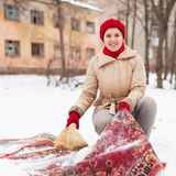 Girl in red cap cleans carpet with snow. In winter day outdoor Stock Photos