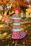 Girl in red cap jumps with an autumn bouquet of leaves royalty free stock photography