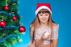 The girl in a red cap sits near an elegant New Year tree and hol Stock Images