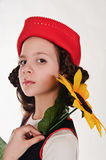 Girl in a red cap with a sunflower Royalty Free Stock Image