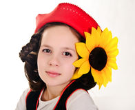 Girl in a red cap and with a sunflower royalty free stock photo