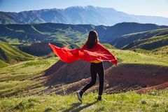 A girl with a red cape on her shoulders runs across the field against the backdrop of the spring mountain landscape stock images