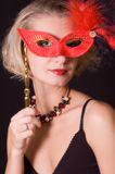 Girl with a red carnival mask. Picture of a girl with a red carnival mask isolated on black Royalty Free Stock Image