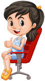Girl on red chair having thumb up Royalty Free Stock Photo