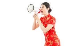 Girl in red cheongsam holding loud speaker. Beautiful girl in red cheongsam holding loud speaker calling for big news for chinese new year sale. isolated on Royalty Free Stock Photography
