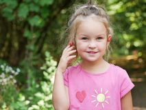 Girl with red cherries on her ears. stock photography