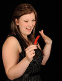 Girl with red chili pepper. A studio portrait of a smiling teenage girl, holding a hot red chili pepper. Black background royalty free stock photo