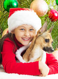 Girl in a red Christmas dress hugging dog Stock Image