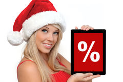 Girl in a red Christmas hat holding tablet Stock Image