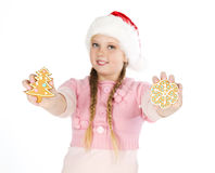Girl in red christmas hat holds gingerbread cookies in hand on w Stock Photo