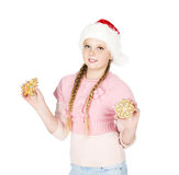 Girl in red christmas hat holds gingerbread cookies in hand on w Royalty Free Stock Photo