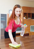 Girl in red cleaning table Royalty Free Stock Image