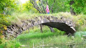 A girl in a red cloak is on an old destroyed bridge.  stock video