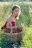 Girl in red clothes. A girl in red clothes with a large basket picks flowers on the field Royalty Free Stock Image