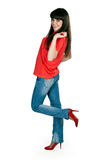 Girl in red clothes and blue jeans in the studio Stock Image